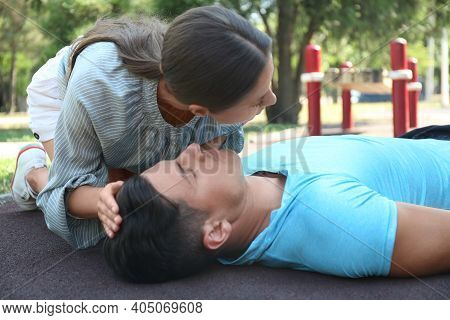 Young Woman Checking For Breathing Of Unconscious Man Outdoors