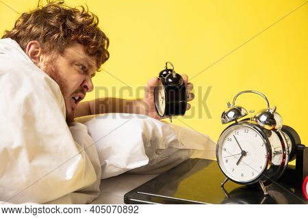 Crazy. Man Wakes Up At His Bed On Yellow Background And Hes Mad At Clocks Ringing, Switches It Off,