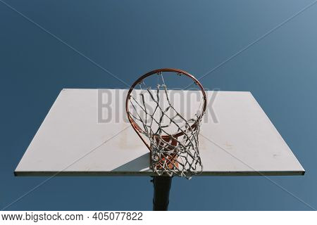 Looking Up At Old Worn Out Basketball Hoop With Torn Net And White Backboard Alone Against Blue Sky.