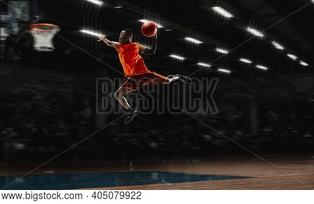 High Dunk. African-american Young Basketball Player In Action And Motion In Flashlights Over Dark Gy
