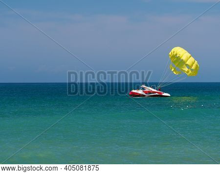 Calm At Sea. A Boat Sits On The Turquoise Surface Of The Water In The Distance. A Parachute Is Attac