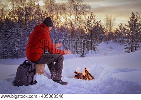 A Man Warms Near The Fire In Snow Covered Forest. Concept Adventure Active Vacations Outdoor. Extrem