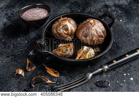 Bulbs Of Fermented Black Garlic In A Pan. Black Background. Top View