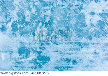 Ice Blue Background With Skate Tracks. Skating Rink. Frozen Water, Sea. Frosty Ice Texture With Scra