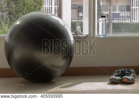 Black Fitness Exercise Ball, Sports Shoes, Water Bottle And Alcohol Sanitizer Spray On The Gym Studi