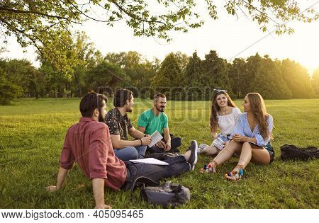 A Group Of Young People Students Communicate Sitting On The Grass In A Summer Park. Friends Relax In