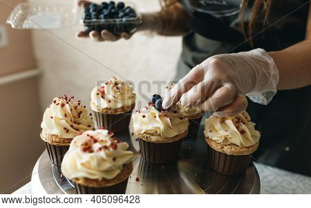 The Chef Girl Decorates Fresh Cupcakes Covered With Vanilla Cream With Berries.sweet Homemade Cupcak
