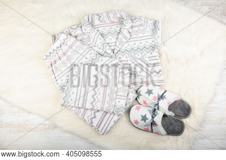 Pair Of Warm Female Slippers And Pajamas On White Furry Carpet.