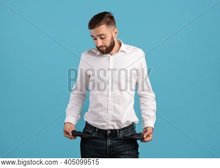 Young Bearded Man Showing Empty Pockets On Blue Studio Background. Millennial Guy Losing Money, Faci