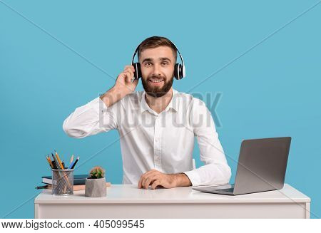 Bearded Male Helpline Operator With Headphones And Laptop Answering Customers Call At Desk Over Blue