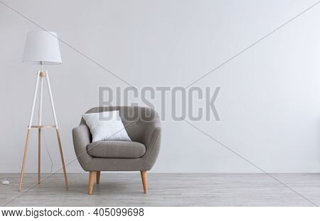 Modern Scandinavian Parlor Or Home Office Interior. Vintage Gray Armchair With White Pillow, Lamp On