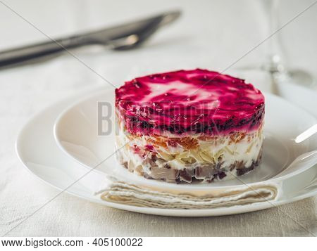 Layered Salad Herring Under Fur Coat On Table. Portion Of Traditional Russian Salad With Herring, Be