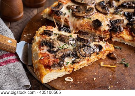 Closeup Of A Slice Of Mushroom And Cheese Pizza On A Baking Stone