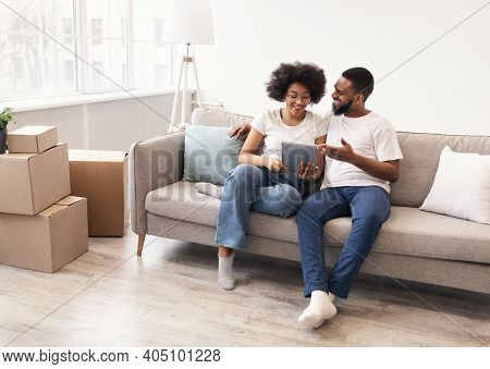 Happy Black Spouses Using Tablet Sitting Among Moving Boxes On Sofa In New Apartment After Relocatio