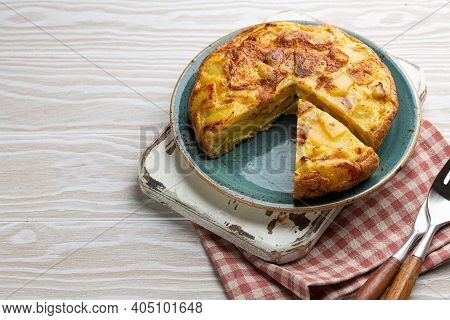 Homemade Spanish Tortilla With One Slice Cut - Omelette With Potatoes On Plate On White Wooden Rusti