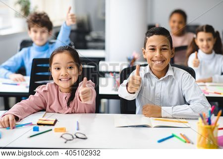 Education Concept. Diverse Group Of Happy Smiling International Classmates Sitting At Desk In Classr