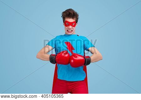 Funny Fearless Young Man In Superhero Costume And Red Boxing Gloves Looking At Camera While Preparin