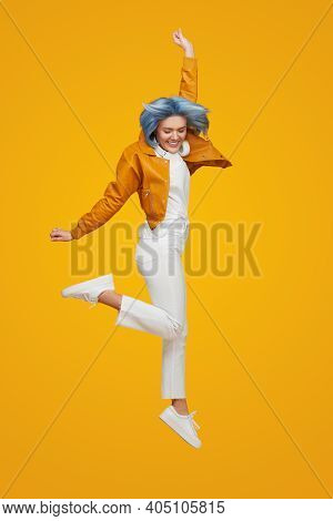 Full Body Happy Young Woman With Blue Hair Raising Arm And Smiling While Leaping Up In Air And Celeb
