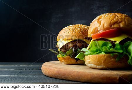 Close Up Two Fresh Tasty Homemade Hamburgers With Fresh Vegetables, Lettuce, Tomato, Cheese Beside S