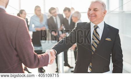 Close Up. Serious Businessman Meeting His Business Partner With A Handshake.
