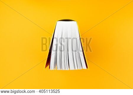 Top View Of Big Book With Yellow Cover On Orange Background