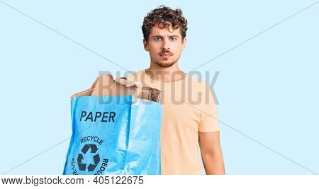 Young handsome man with curly hair holding recycling wastebasket with paper and cardboard thinking attitude and sober expression looking self confident