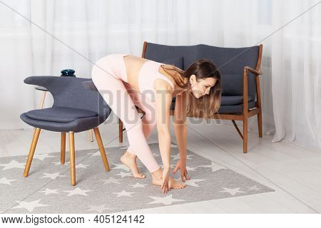 Slender Woman In Pink Tracksuits Stretches To Her Leg Sitting On The Back Of A Gray Padded Chair In