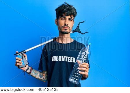 Young hispanic man holding plastic bottle and litter picker to recycle relaxed with serious expression on face. simple and natural looking at the camera.