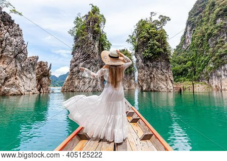 Back View Of Young Female Tourist In Dress And Hat At Longtail Boat Near Three Rocks With Limestone