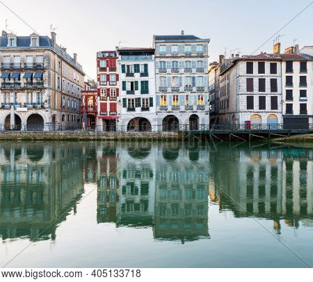 Old traditional building facades and their reflections in the Nive River at sunrise in Bayonne, France.
