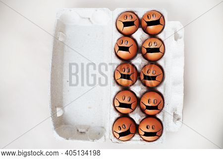 Chicken Eggs With Drawn Medical Mask On Egg Carton On White Background. Easter Eggs Holidays Decorat