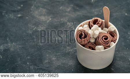 Rolled Ice Cream With In Cone Cup On Dark Rustic Background. Iced Rolls With Chocolate. Thai Style C