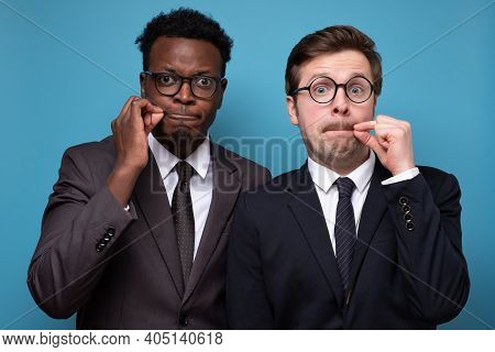 Two African And Caucasian Men Shut Mouth As Zip With Fingers
