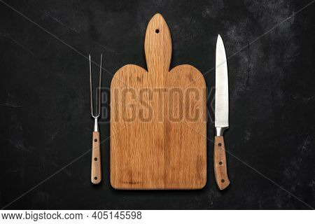 Empty Wooden Cutting Board, Meat Fork And Knife On Black Stone Background. Top View, Flat Lay, Copy