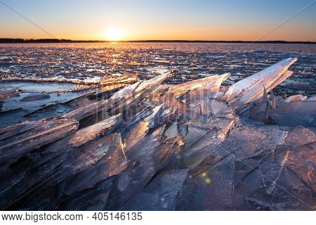 Ice On A Frozen Lake In Sunlight At Sunset. Winter Nature Landscape. Scenery Icy Crystalline Structu