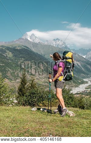 Young Caucasian Woman Hiker From Behind With Backpack Hiking On Mountain Trail In Summer In Green Ca