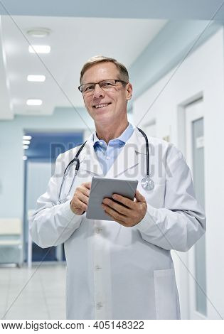 Old Senior Male Professional Doctor Physician Holding Digital Tablet Computer Looking At Camera In H