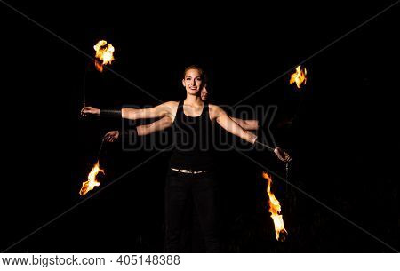 Happy Couple Of Fire Performers Spin Burning Pois At Night Dark Outdoors, Action