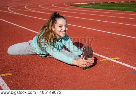 Sporty Beauty. Confident Flexible Athlete. Teen Girl Warming Up On Stadium. Kid In Sportswear Stretc