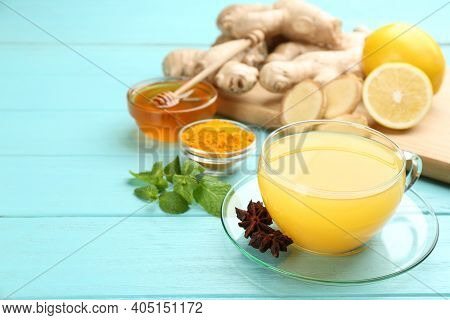 Immunity Boosting Drink And Ingredients On Turquoise Wooden Table. Space For Text