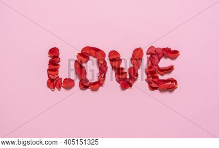 Love Written With Red Rose Petals, Isolated On Pink Background. Top View With Rose Petal Love Word.