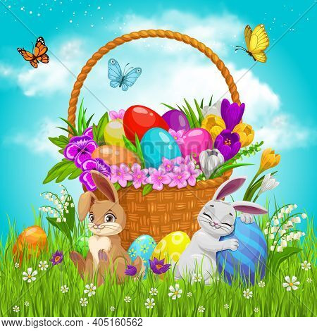 Easter Basket With Flowers, Painted Eggs And Bunnies On Green Lawn With Flying Butterflies Under Clo