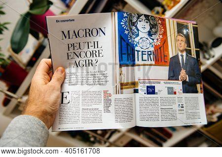 Paris, France - Feb 21, 2019: Pov Male Hand Holding French Magazine With Portrait Of Emmanuel Macron