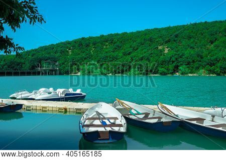 Several Rowing Boats On The Shore Of A Beautiful Lake. Rowing Boats In Turquoise Water On A Backgrou