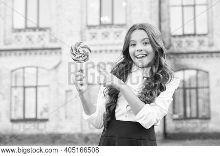 Girl With Curly Hair Pointing Finger On Lollipop. Sweet And Candy. Happy Little Girl In Classy Unifo