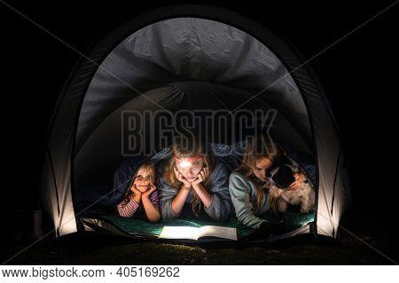 Girls laying with dog in a camping tent at night wrapped in a sleeping bag. Children reading a book with flashlight. Summer holidays concept