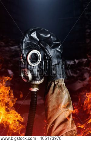 Photo Of Stalker Hand In Rubber Glove And Jacket Holding Soviet Gas Mask In Flames On Ruined Backgro
