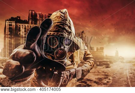 Photo Of A Stalker In Jacket And Gloves In Damaged Gas Mask With Filter Reaching Out His Hand To Cam
