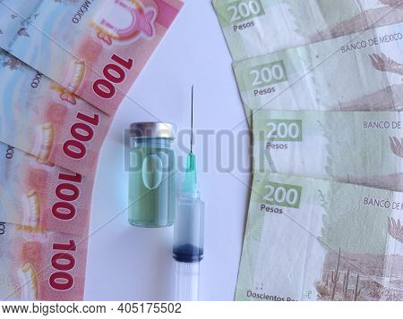 Syringe, Bottle With Medicine And Mexican Banknotes