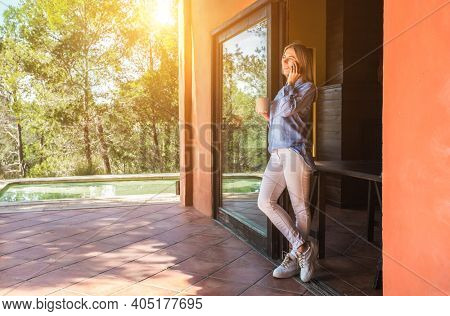 Working from home. Woman talking on video call with Family, using smartphone and drinking tea. Online chat. Spend free time on terrace. Staying connected, Social distancing, internet, chatting. Work.